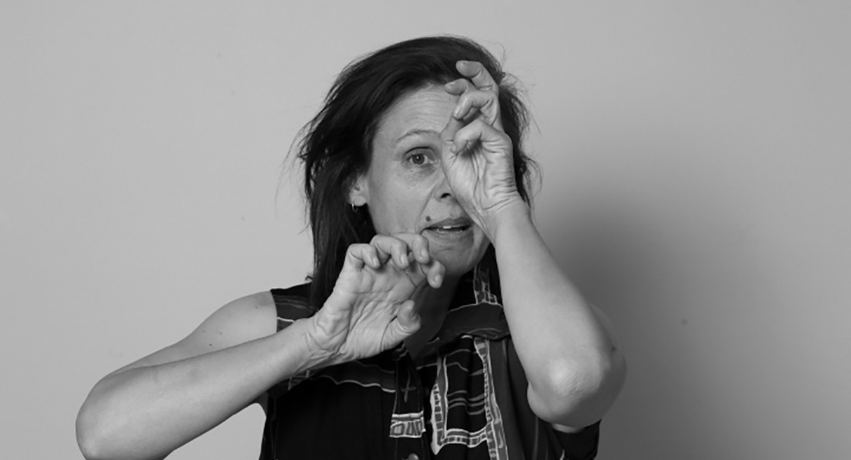 Portrait of Vicki Van Hout in black and white with one hand over her eye, and the other like a claw