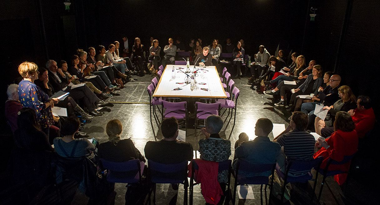 image of lois weaver and her long table. a table sits in the middle of the room with a circle of participants sitting around in chairs