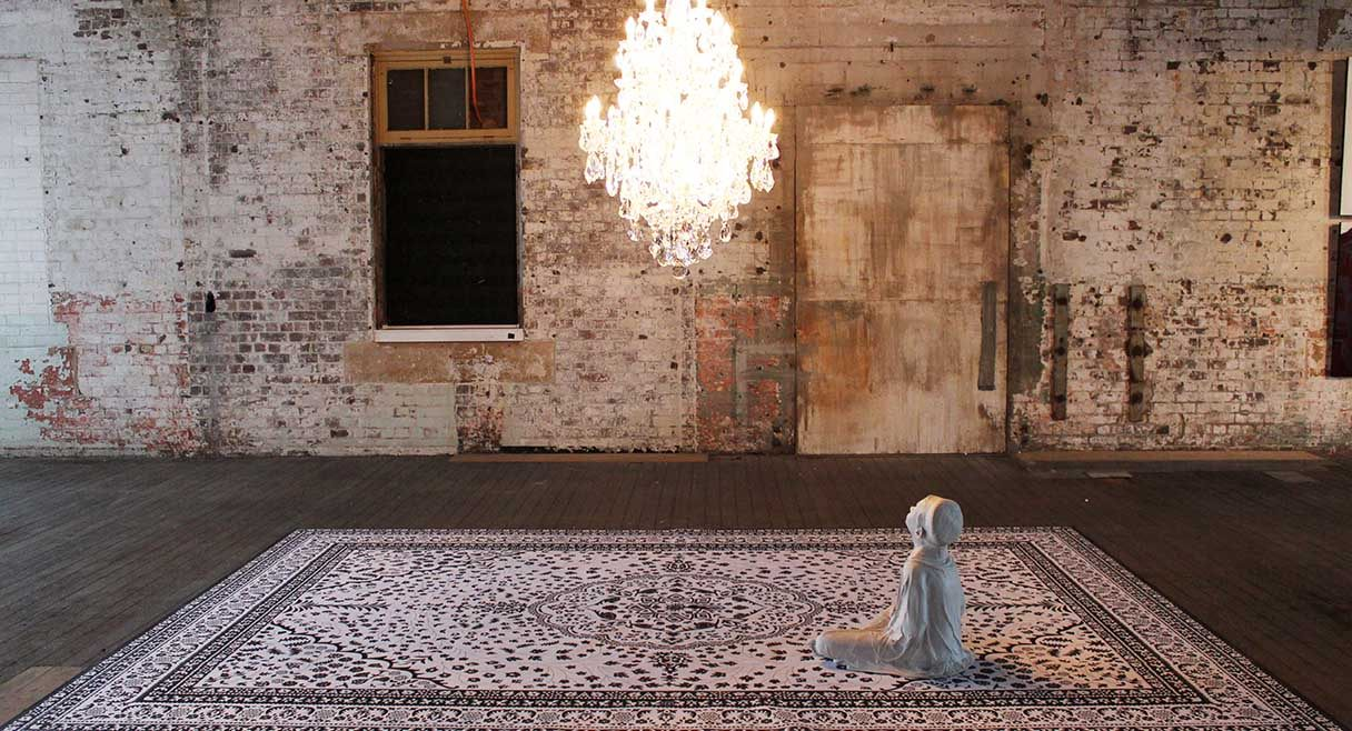 image of a young body sitting on a rug shrouded in white sitting under a chandelier
