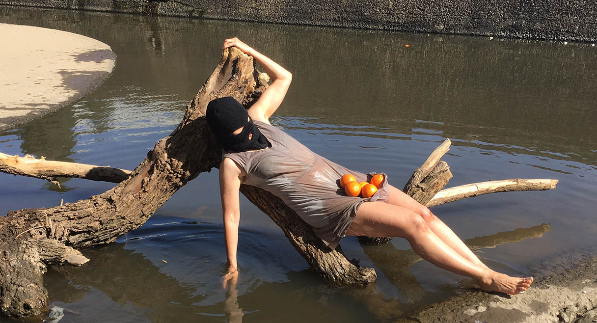 woman in a grey dress lies on a stump in a river she has a black mask with oranges in her lap