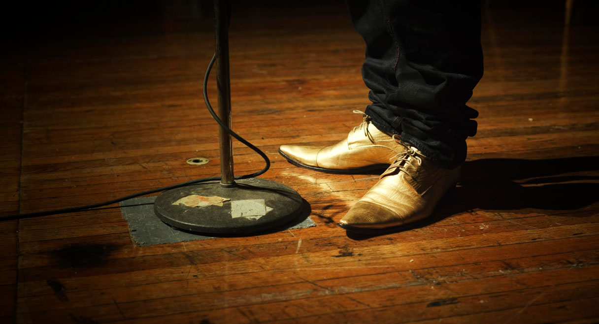 Image of a stage with a pair of gold shoes and a microphone stand