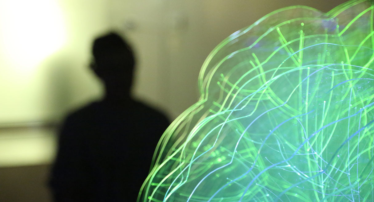 man in shadow with a green electrical bulb in the corner like a brain