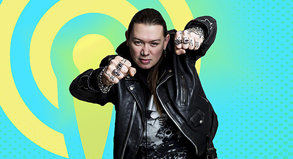 man in leather jacket punching his tattoed fists into the air